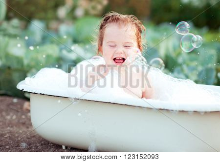 Smiling baby girl washing in bath outdoors. Laughing child. Childhood.