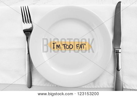 Piece of paper with text I'm TOO FAT in plate on wooden table with knife and fork, top view