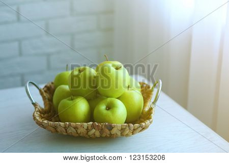 Ripe green apples in a wicker basket on a kitchen table