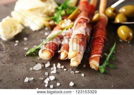 Bread sticks grissini with prosciutto ham and mozzarella cheese, close up