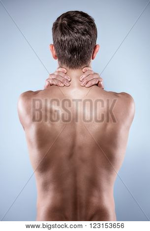 Studio shot of handsome young man with naked torso. Man suffering from neck ache. Back view photo