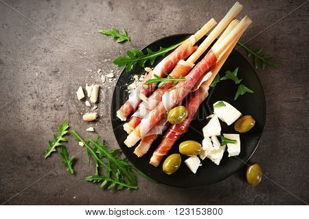 Bread sticks grissini with prosciutto ham on a plate, top view