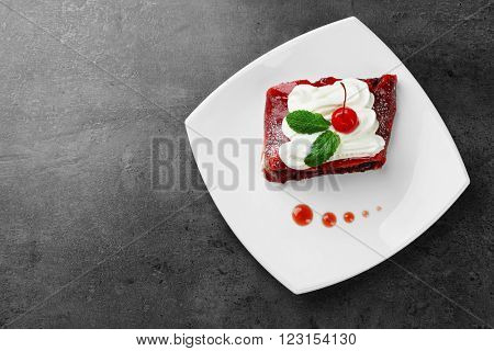 Delicious cherry strudel with mint and cream on plate