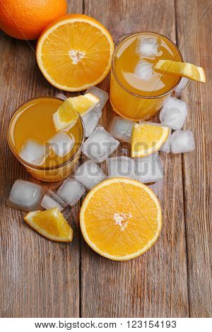 Two orange juices with cubes of ice and orange on wooden table background