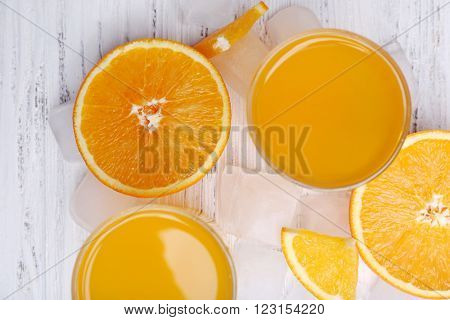 Orange juice with cubes of ice and orange, closeup