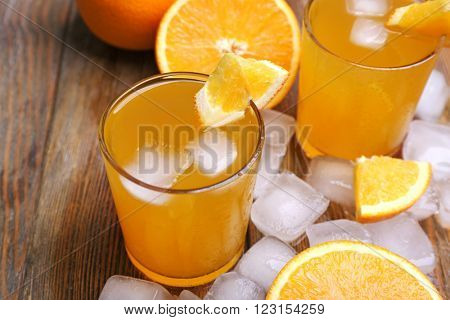 Two orange juices with cubes of ice and orange, closeup