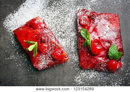 Two slice of powdered cherry strudel with mint