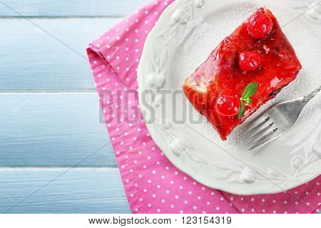 Cherry strudel with mint and fork on wooden table