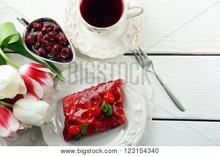 Cherry strudel with mint and cup of tea on wooden table