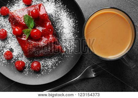 Powdered cherry strudel with mint and cup of coffee