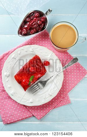 Cherry strudel with mint and cup of coffee on wooden table