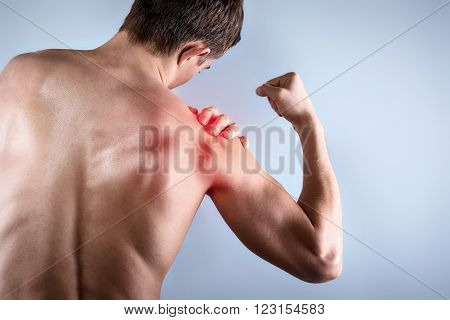 Studio shot of handsome young man with naked torso. Man suffering from shoulder ache. Red spot on shoulder