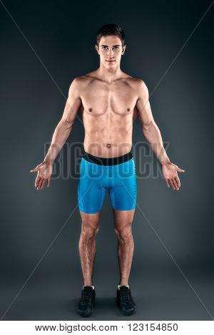 Studio shot of handsome young sportsman with naked torso. Muscular man looking at camera