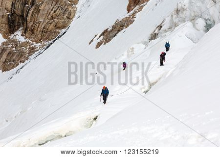 Members of Alpine Expedition Walking Up on Steep Snowfield Using Ice Climbing and Hiking Gear Dangerous Crevasses Rope Belay Led by Mature Guide