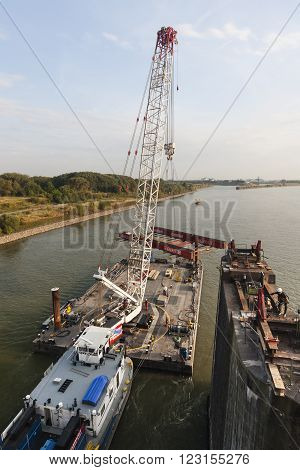 WESEL - SEPTEMBER 10: Floating crane carrying girder platform to support a bridge deconstruction on Rhine river, Germany on September 10, 2012