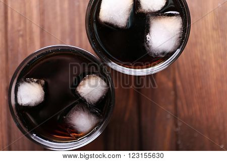 Cocktails with ice blocks  on wooden background, top view