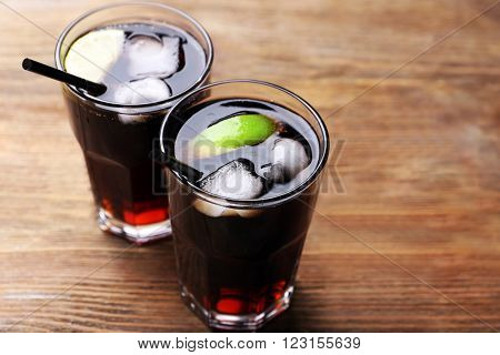 Cocktails with lime slices and ice blocks on wooden table, close up