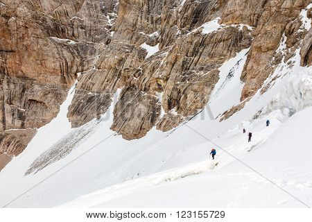 Members of Alpine Expedition Walking Up on Steep Snowfield Dangerous Crevasses Rope Belay Steep Rock Wall on Background