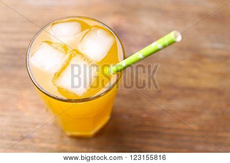 Glass of orange juice with ice blocks and tubule on wooden background