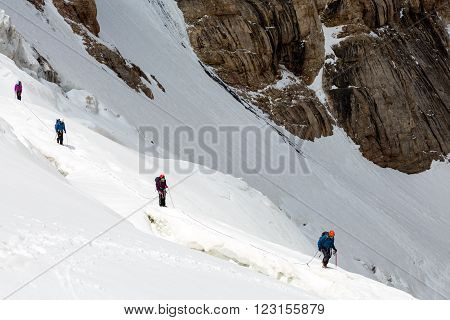 Members of Mountain Expedition Walking Along Dangerous Ice Crevasse on Steep Snowfield Rock Wall on Background