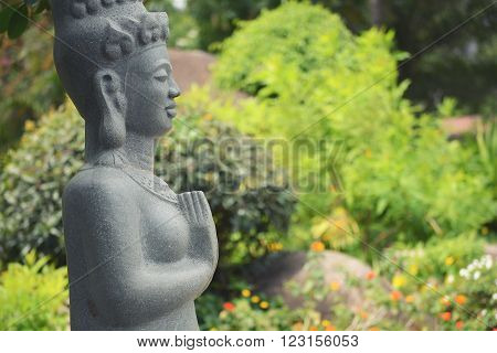 buddha statue seating in the park and doing meditation