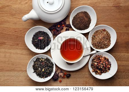 Tea concept. Cup of tea with teapot and different kinds of dry tea on wooden table, close up