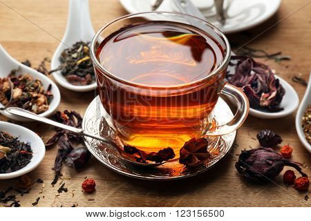 Tea concept. Different kinds of dry tea in spoons. Glass cup of tea on wooden background