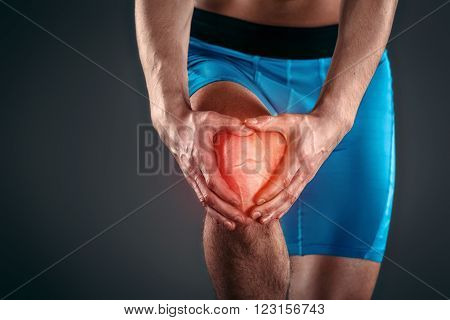 Studio shot of handsome young sportsman with naked torso. Muscular man suffering from pain in knee. Red spot on knee