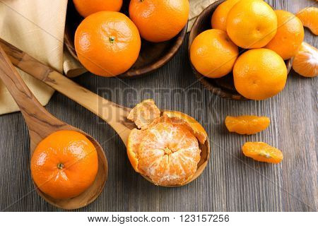 Fresh delicious  peeled and unpeeled tangerines on the wooden spoons, top view