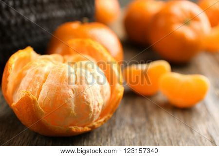 Fresh, delicious peeled and unpeeled tangerines with slices beside wicker basket on the rustic table, close up