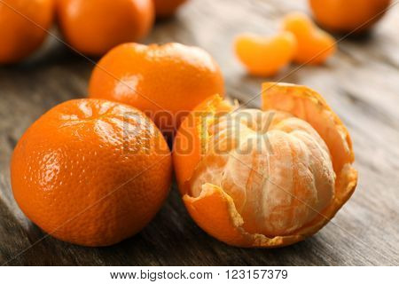 Fresh, delicious tangerines peeled and unpeeled on a rustic table, close up