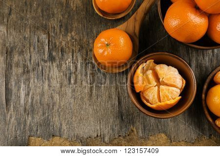 Fresh, delicious tangerines  in different conditions, peeled and unpeeled in wooden bowls and spoons on the rustic table, top view