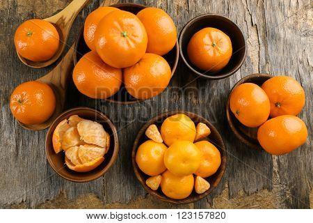 Fresh, delicious tangerines  in different conditions, peeled, unpeeled, sliced in wooden bowls and spoons on the rustic table, top view