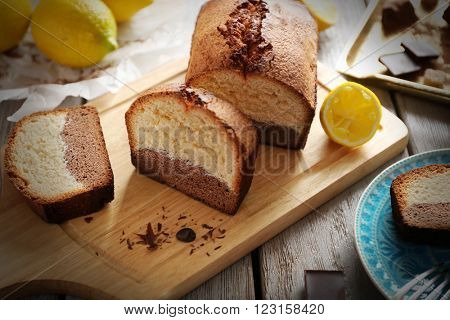 Composition of tasty cake with chocolate morsels and lemon on grey wooden background