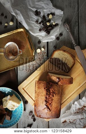 Composition of tasty cake with chocolate morsels on grey wooden background, top view