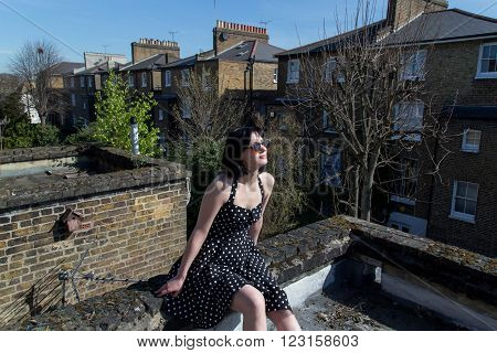 Girl in black polka dot dress and sunglasses sitting on the roof of the second floor of a house in London. She takes sun baths in the spring.