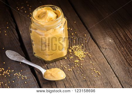 Fresh mustard sauce in a jar and mustard seeds scattered on the old wooden background