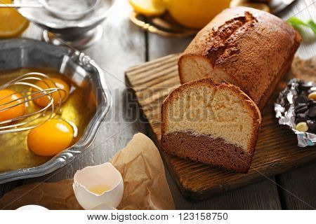 Composition of tasty cake with chocolate morsels and broken eggs on grey wooden background