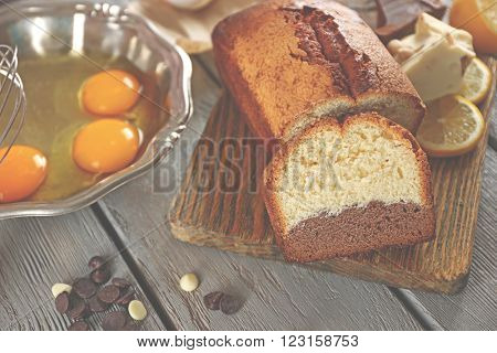 Composition of tasty cake with broken eggs and chocolate morsels on grey wooden background