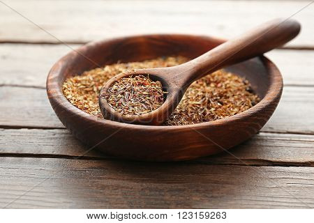 Rooibos tea in a round bowl on wooden table, close up
