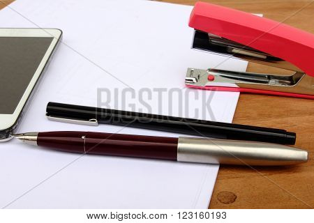 Pen and stapler on the table focus at the pen