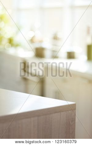 Light wooden kitchen table on blurred background, close up