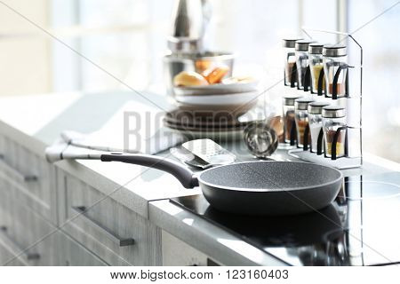 Pan on modern electric stove in the kitchen beside window