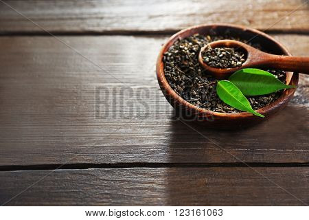 Granulated tea with green leaves in wooden bowl on table closeup