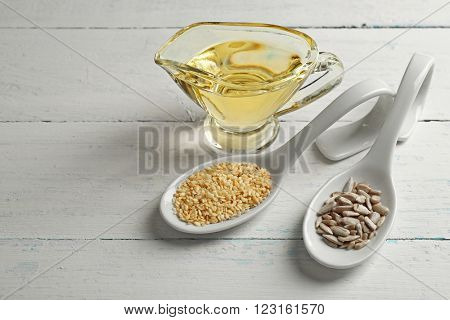Flax and sunflower seeds with oil on wooden table