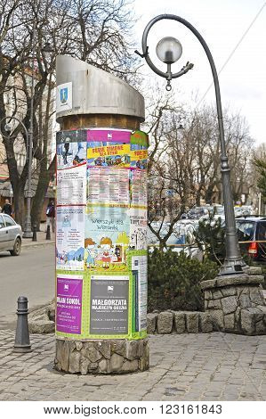 ZAKOPANE, POLAND - MARCH 09, 2016: Advertising column placed next to Krupowki street. An advertising column presents posters and billboards on it. Advertising pillar is one way of outdoor advertising