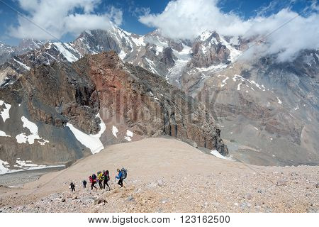 Group of People in Sporty Style Clothing with Backpacks and Walking Poles Mountain Landscape with Blue Sky and Clouds on Background