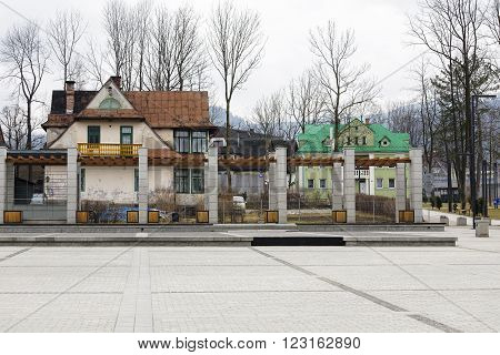 ZAKOPANE POLAND - MARCH 07 2016: View over the Independence Square towards old residential house built about 1910 on the left and building of the former Municipal Baths built in 1928 on right side