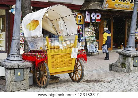 ZAKOPANE POLAND - MARCH 09 2016: Sales of Oscypek cheeses and other regional food products at Krupowki street since February 02 2007 oscypek is Polish regional product protected by EU law