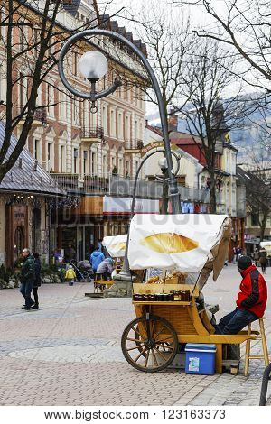 ZAKOPANE POLAND - MARCH 09 2016: Sales of Oscypek cheeses and other regional food products at Krupowki street oscypek is Polish regional product protected by EU law since February 02 2007